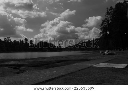 A lake with a beach under a cloudy sky. - stock photo