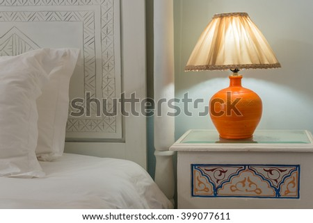 A lamp on a nightstand next to a bed with a white carved headboard - stock photo