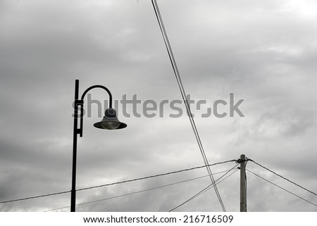 A lamppost and some electric clable on a cloudy sky in the suburb of a city - stock photo