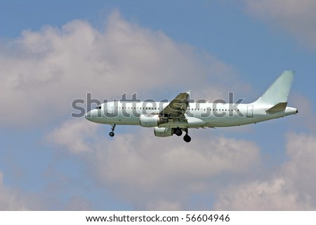A landing airplane with blue sky and clouds background. - stock photo