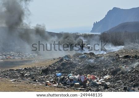 A landscape on scrap-heap in smoke. - stock photo