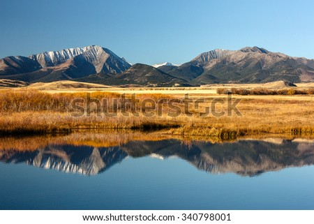 A landscape photograph of western mountains reflected in a body of water. - stock photo