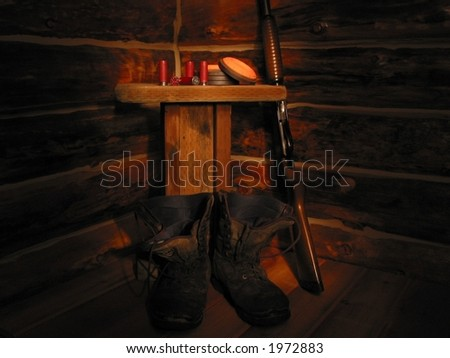 A landscape view of a shotgun, boots and a table in the corner of a log building. - stock photo