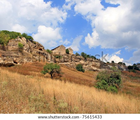 A landscape with ancient brick building, the Chufut-Kaleh Cave Town near Bakhchisarai in the Crimea - stock photo