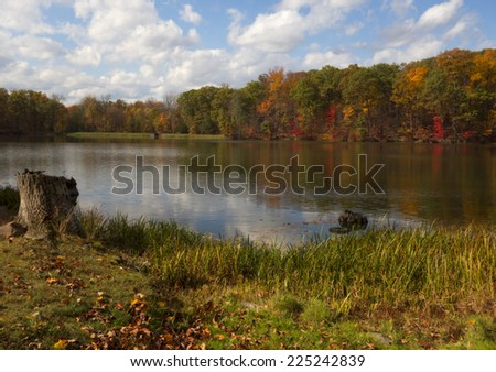 A landscape with colorful Autumn foliage reflected in lake. - stock photo