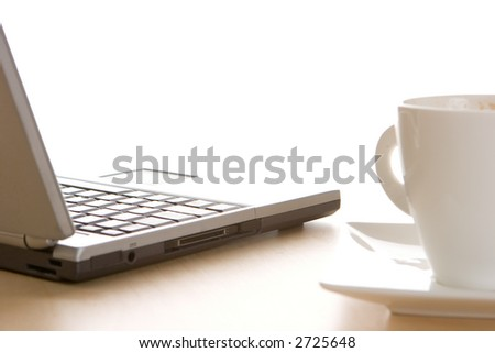A laptop and a cup of coffee - stock photo