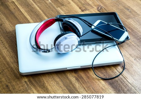 A Laptop computer, Headphones, a Tablet PC and a Smartphone on a wooden Desktop.  - stock photo