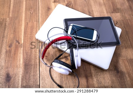 A Laptop computer, Headphones, a Tablet PC and a Smartphone on a wooden Desktop.
