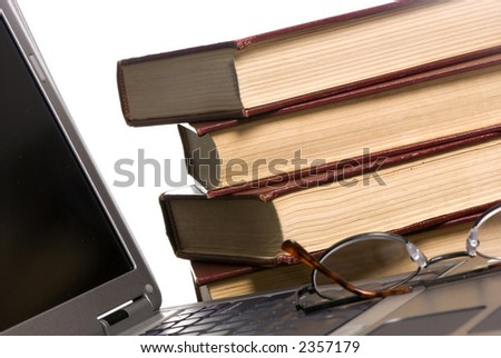 A laptop computer on a table with several study books in the background. - stock photo