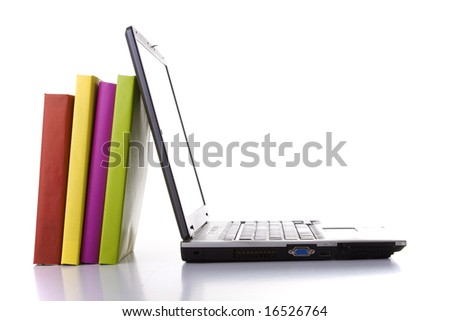a laptop next to a stack of colorful books - stock photo