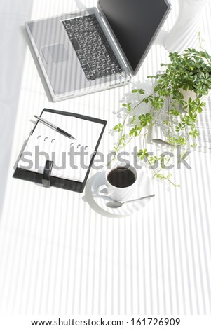 A laptop, notebook, and coffee cup sit on a white desk. - stock photo