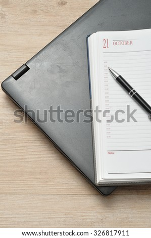 A laptop with a pen and an open diary - stock photo