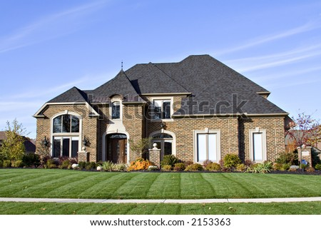 A large American brick home with many roof angles and windows. - stock photo
