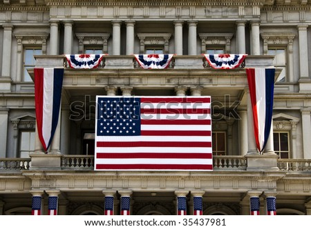 A large American flag and various 4th of July decorations in front of a building in Washington DC.