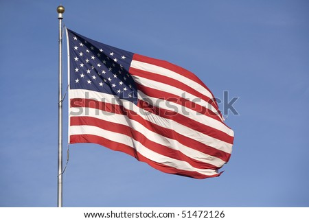 A large American flag waves in the wind on a bright and sunny day.