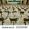 A large amount of empty seats with tables in a lecture hall - stock photo