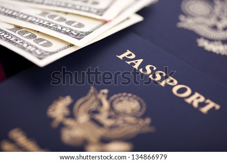 A large amount of 100 US dollar money notes on top of a stack of American and German passports. Shallow depth of field. - stock photo