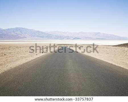 A large and straight road at Death Valley National Park - stock photo
