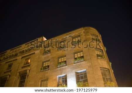 A large apartment building at night lighted with a lamp. - stock photo