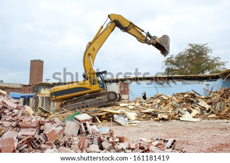 A large backhoe demolishes an old building - stock photo