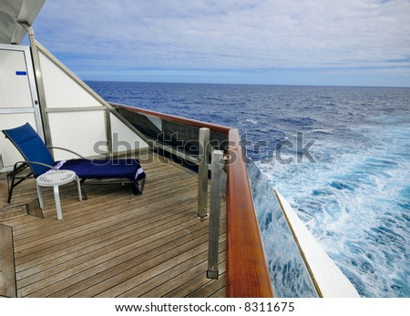 A large balcony overlooks the wake of a cruise ship at sea - stock photo