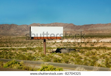 A large blank billboard by a road in the desert - ready for your own message! - stock photo