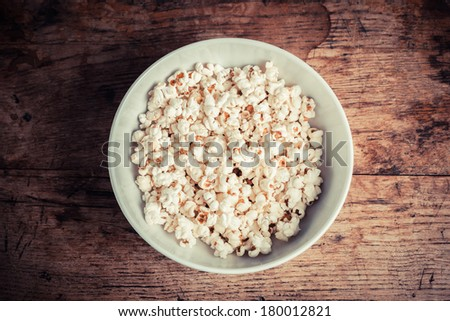 A large bowl of popcorn on a wooden table - stock photo
