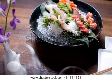 A large bowl of sashimi in a dinner setting - stock photo