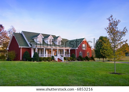 A large brick house in the country at dusk. - stock photo