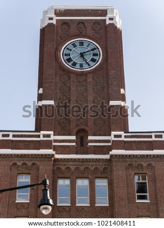 A Large Brick Tower With Clock On The Side Of Building