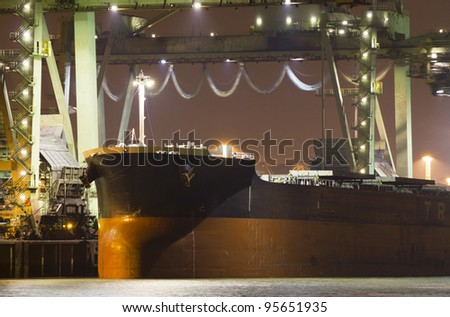 A large bulk carrier is supplying iron-ore to the harbor of Rotterdam, the Netherlands - stock photo