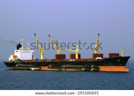 a large bulk carrier loaded with ship cranes work on the roads - stock photo