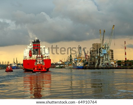 A large cargo ship enters the port escorted by tugboats. Gdansk, Poland. - stock photo