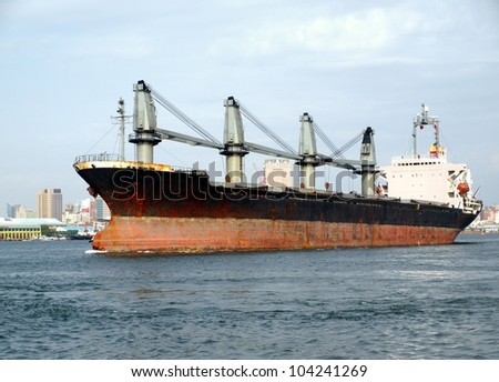 A large cargo ship moves towards the exit of Kaohsiung harbor