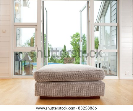 A large chair cushion in front of a large open window - stock photo