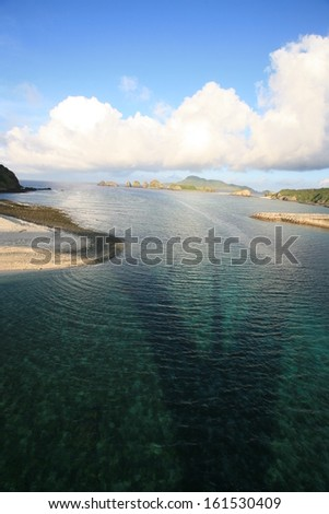 A large clear lake with several shores surrounding it, and a shadow cast by a bridge. - stock photo