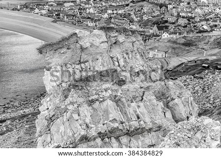 A large cliff topple at the northern end of the Isle of Portland, Dorset, England with houses of the small town and Chesil Beach in the background in monochrome.