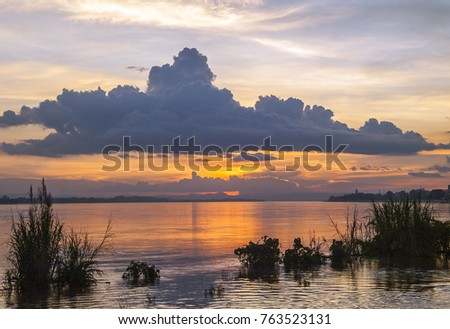 A large cloud hangs over the Mekong River at sunset, Vientiane, Laos