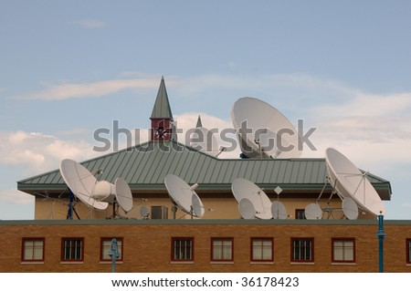 a large collection of communication and broadcast satellite dishes on a rooftop - stock photo
