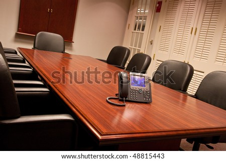 A large conference room table shot from a low angle with a business phone on the end