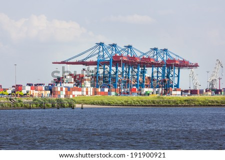 A large container harbor with tall cranes and lots of containers in Hamburg Harbor, Germany - stock photo