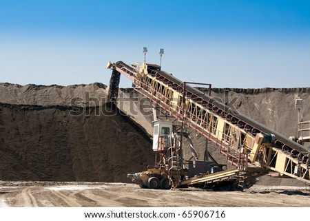 a large conveyor belt carrying golden ore and emptying onto a huge pile - stock photo