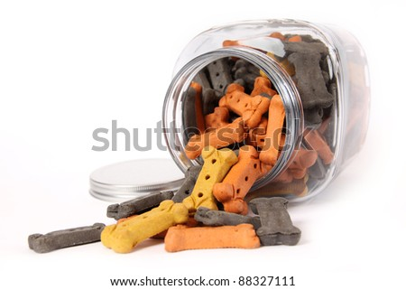 A large cookie jar spilling it's contents of colorful dog treats.