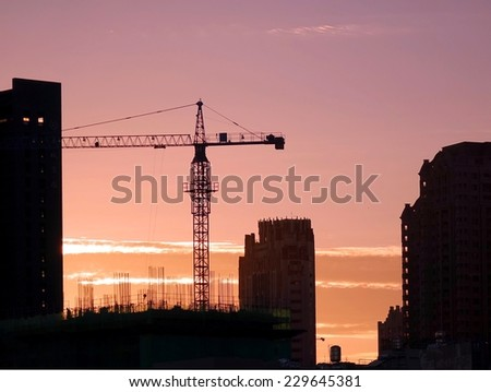 A large crane and construction site seen in silhouette during a beautiful sunset  - stock photo