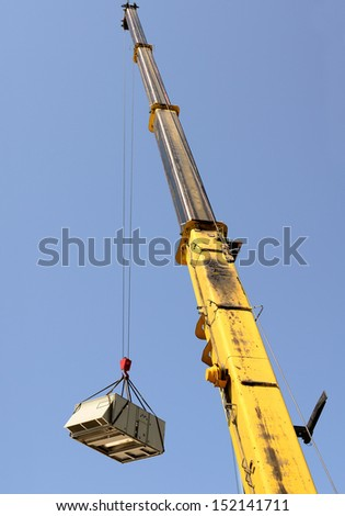A large crane being used to remove a air conditioning unit from a commercial building - stock photo