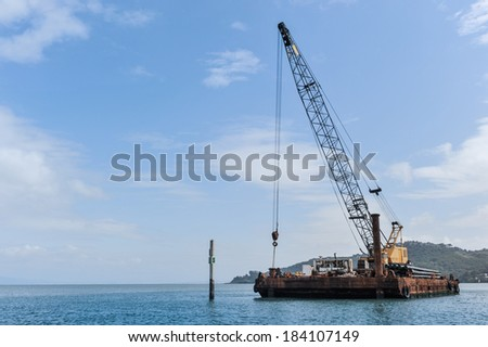 A large crane sits on a barge in a bay with hills behind it - stock photo