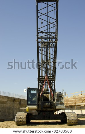 A large crane with one hundred feet of boom on construction project