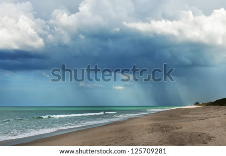 A large dramatic cumulus storm cloud with pouring rain in the distance over the Atlantic Ocean along the shoreline