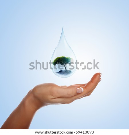 A large drop of water with tree inside  and hands to support it. The symbol of environmental protection. - stock photo