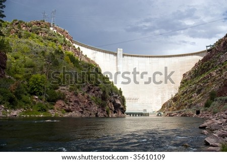 A large, electricity producing dam on a river. - stock photo